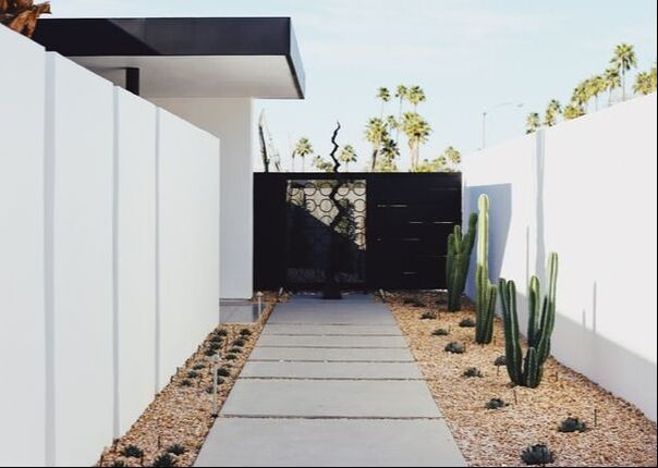 modern landscaping with white rock and pops of greenery alongside a white fence